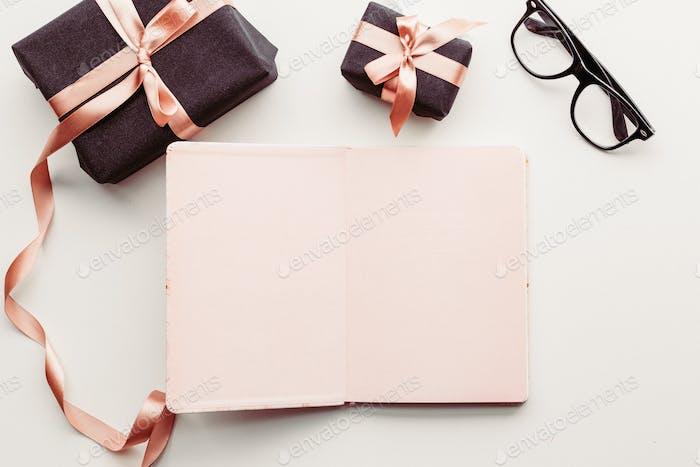 Notizbuch, Augenbrillen und Geschenkbox auf weißem Hintergrund.