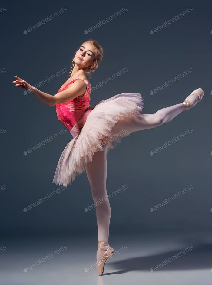 Beautiful female ballet dancer on a gray background