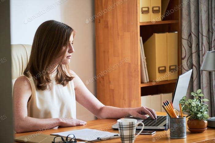 Moderne Geschäftsfrau mit Laptop am Tisch