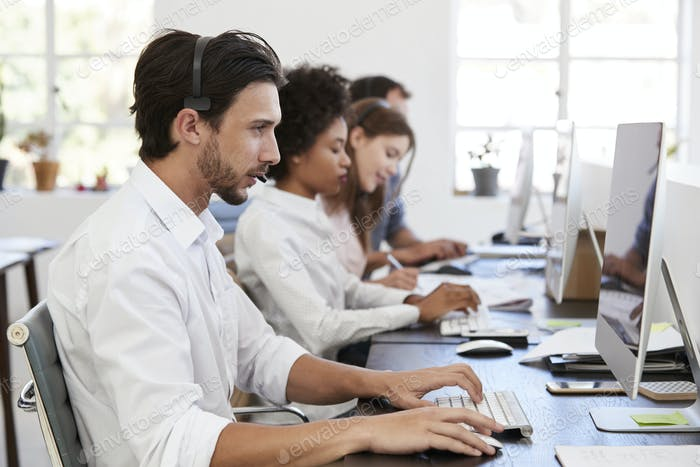 Hispanic man with headset on working at computer in office