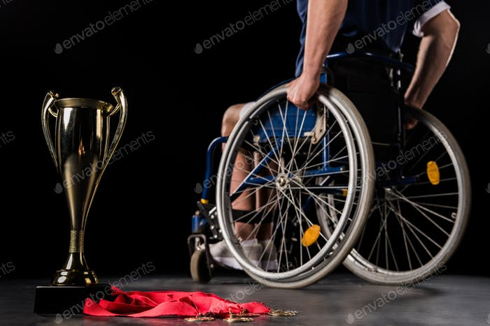 cropped view of paralympic in wheelchair going away from his champion goblet and gold medals