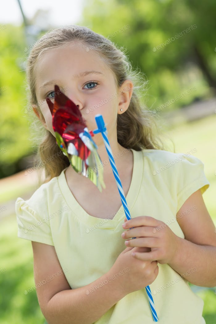 Close-up portrait of cute girl holding pinwheel at the park