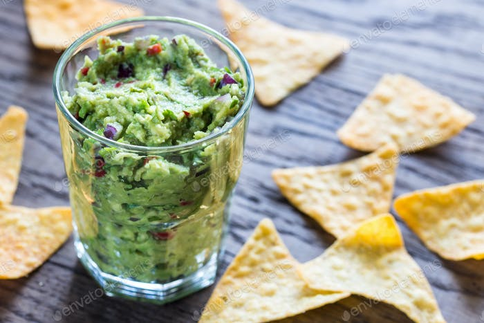Guacamole with tortilla chips on the wooden table