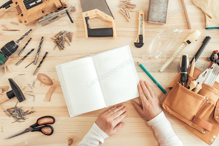 Female carpenter reading DIY project instruction manual