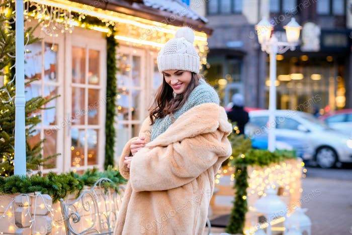 Brunette girl wearing a winter hat and fur coat sitting on a bench