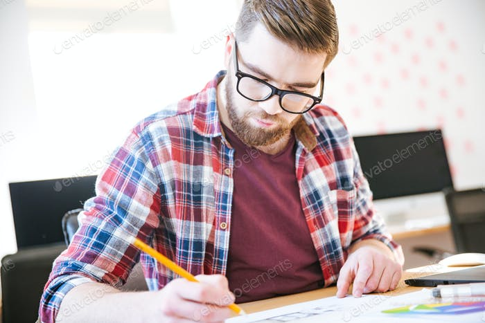 Concentrated young man making sketches with pencil