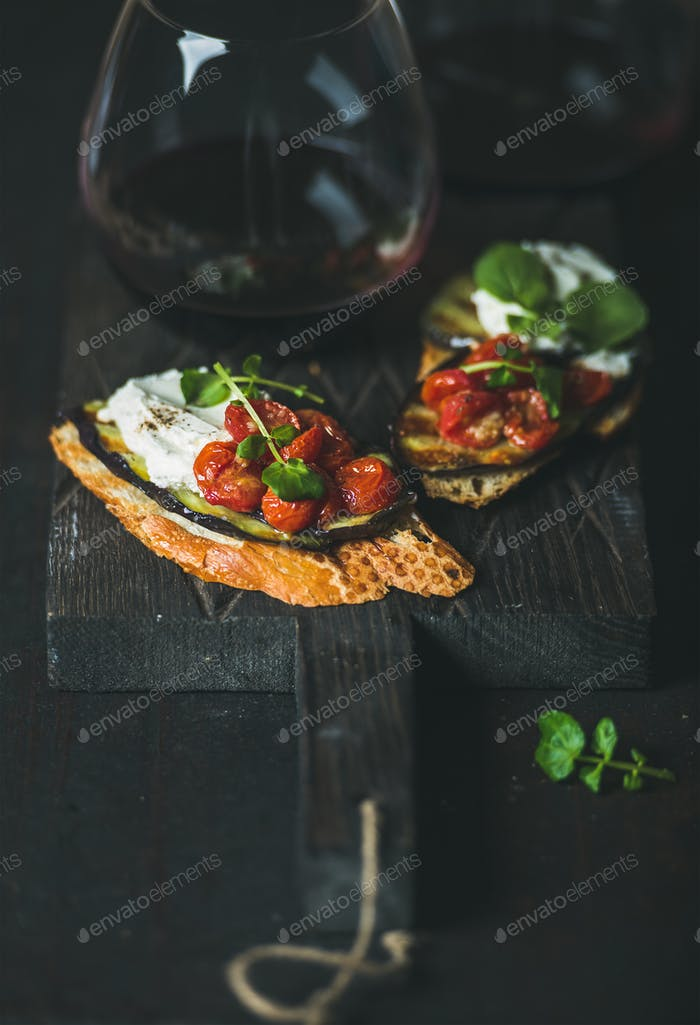 Red wine in glass and brushetta with vegetables, cream-cheese, arugula