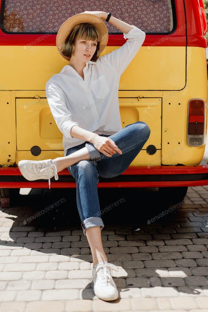 Stilvolle junge Frau in einem Strohhut in weißem Hemd und Jeans sitzt auf der Stoßstange eines hellen