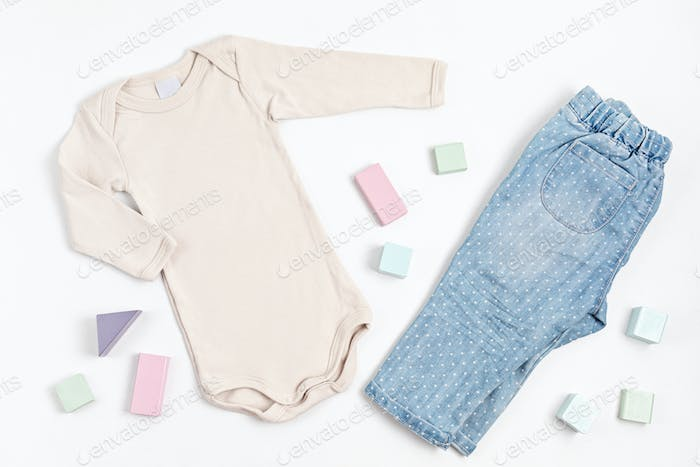 Composition with baby beige bodysuit, jeans, and toy building blocks on white background. Gender