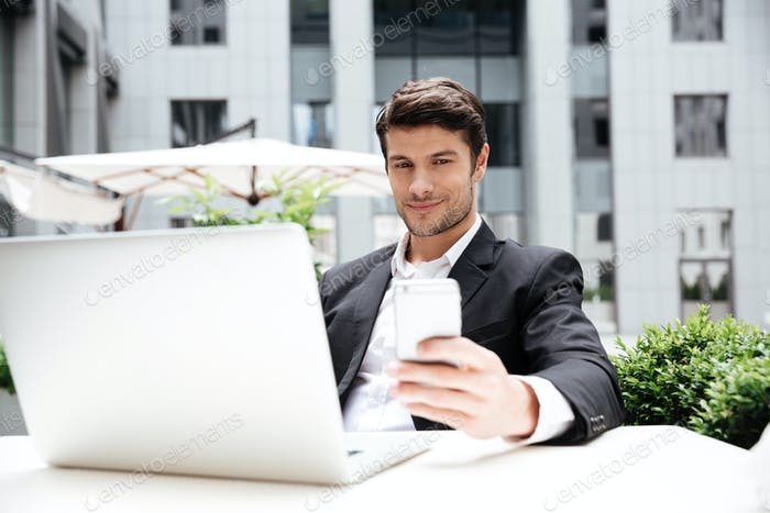 Smiling young businessman with laptop sitting and using mobile phone