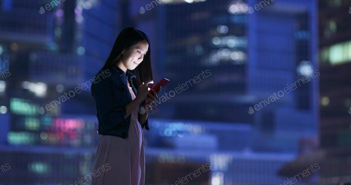 El uso de la mujer del teléfono móvil sobre el fondo de la construcción de negocios
