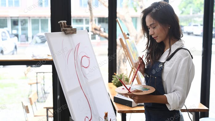 Pretty talented female painter painting on canvas in art studio.