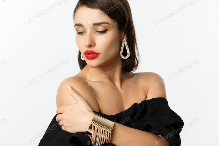 Концепция моды и красоты. Элегантная женщина с красными губами, черное платье, показывая серьги и ювелирные изделия