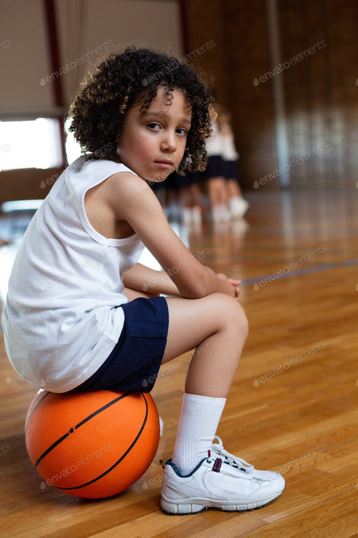 Schoolboy sitting on a basketball and looking at camera in basketball court at school