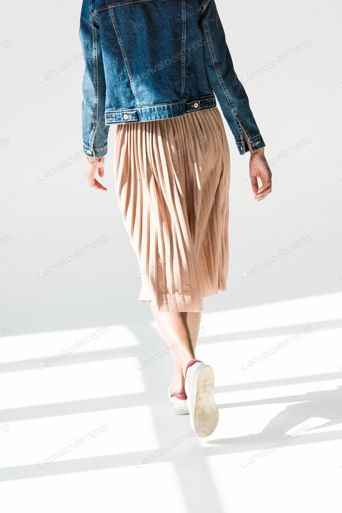 Rear view, low angle shot of woman in beige skirt and denim jacket walking in white studio