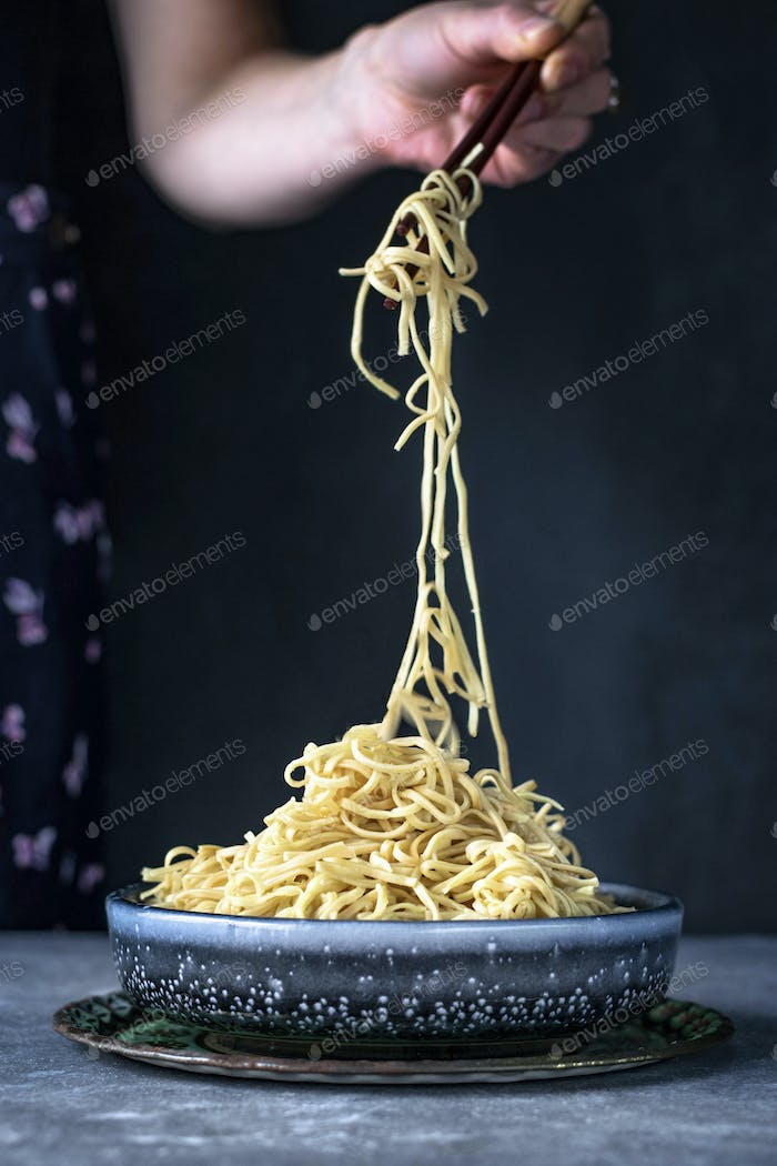 Woman eating Asian egg noodles with chopsticks food photography