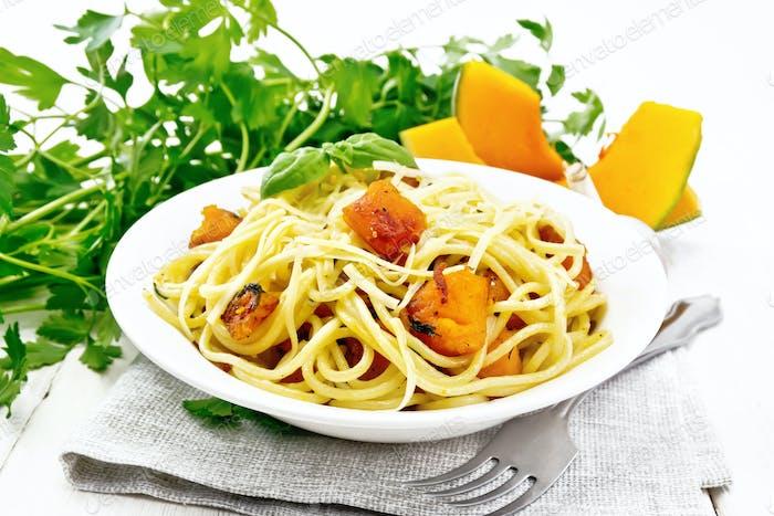 Spaghetti with pumpkin in plate on board