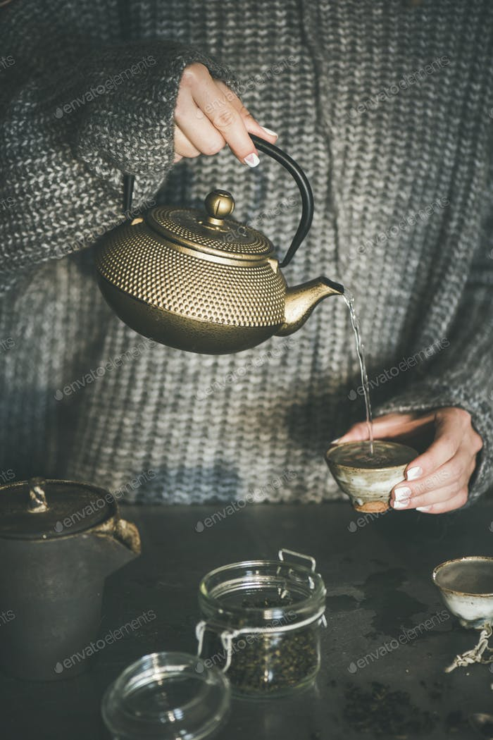 Female in sweater pouring green tea from pot into cup