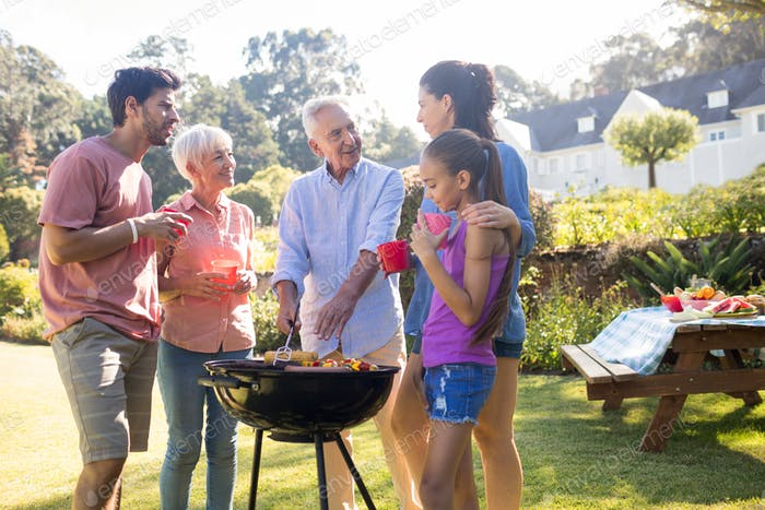 Family talking while preparing barbecue in the park