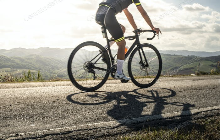 Cyclist sports on road. Sun Rays and shadows from the bike on th