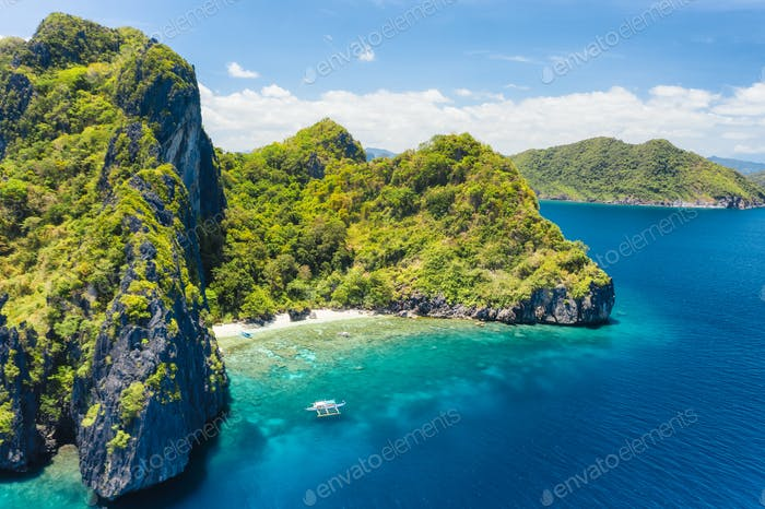 Aerial drone view of tropical beach with lonely boat on Entalula Island. Karst limestone formation