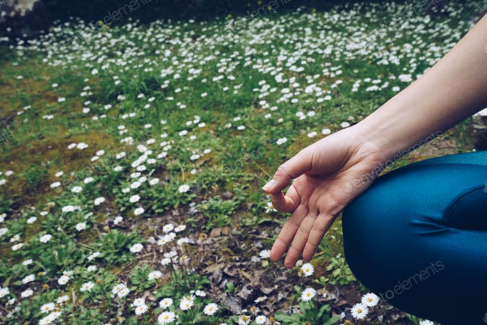 Young woman is sitting in lotus pose, outdoors in spring time wi