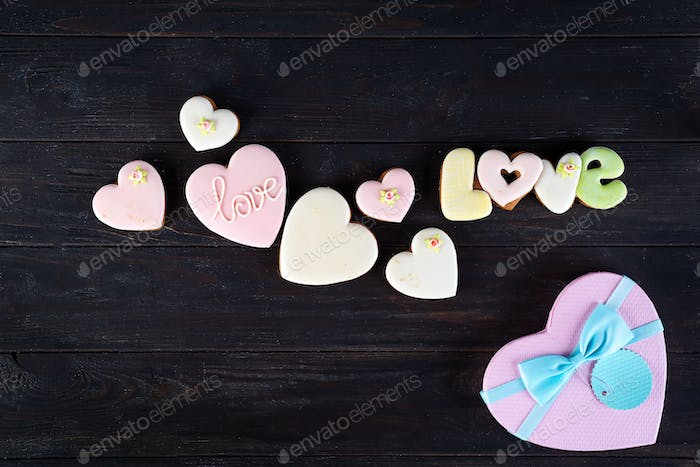 Sweets on Valentine's Day. Cookies in shape of heart and with lettering Love on dark wooden