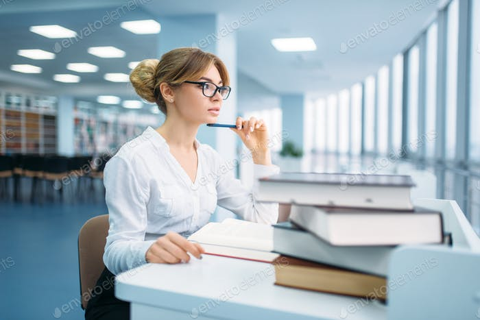 Pretty woman in glasses learning book, library