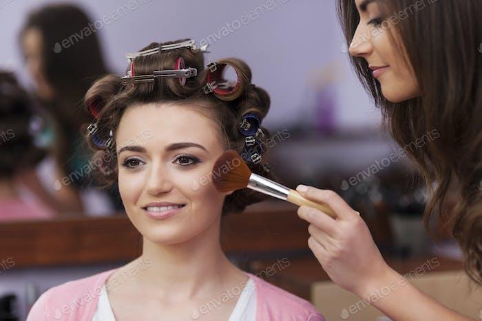 Makeup artist applying makeup by brush