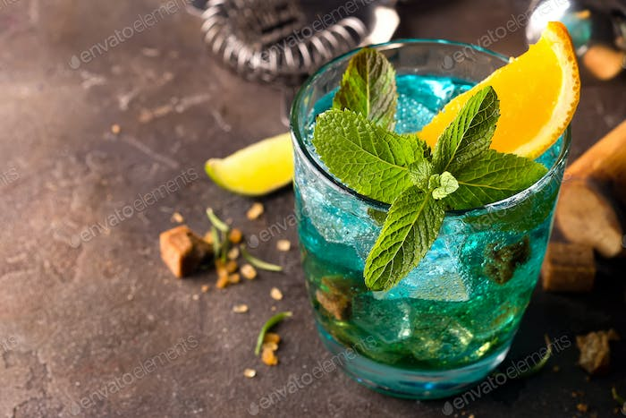 Blue Lagoon cocktail with ice, mint and slice orange on dark stone background, close up