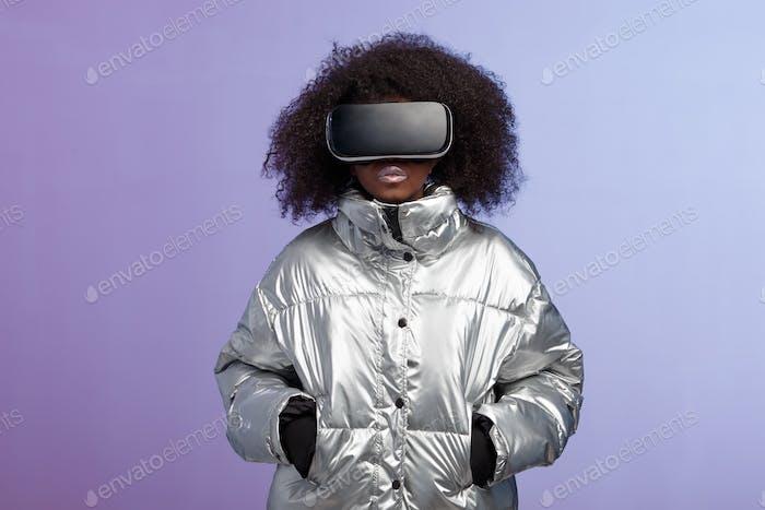 Moderne lockige braunhaarige Mädchen in einer silberfarbenen Jacke gekleidet verwendet die Virtual Reality Brille