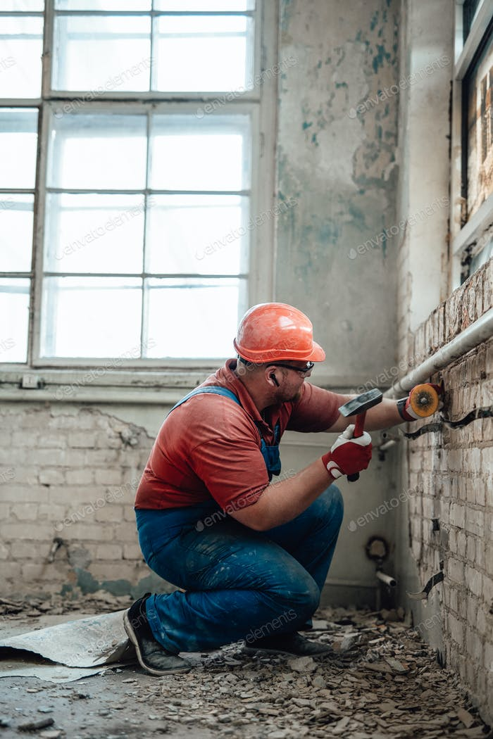 Plump builder on a construction site working on a brick wall with a hammer