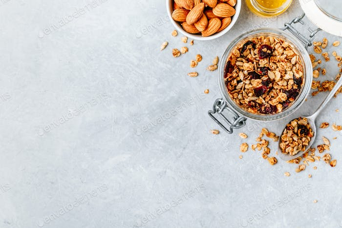 Gesundes Frühstück Müsli mit Mandeln und Honig auf grauem Stein Hintergrund