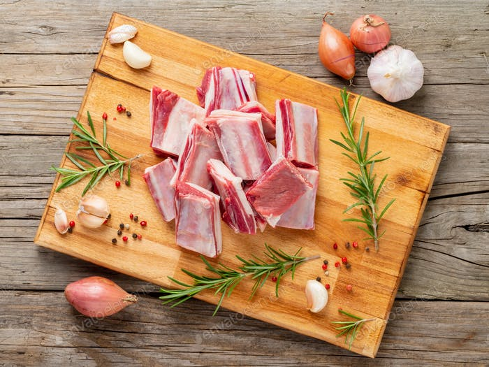 Small pieces of raw lamb ribs on wooden chopping Board