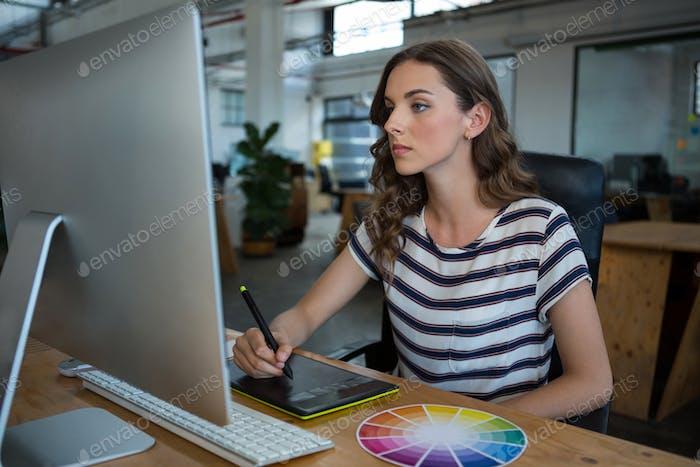 Diseñador gráfico Mujer Uso tableta Gráficos en el escritorio