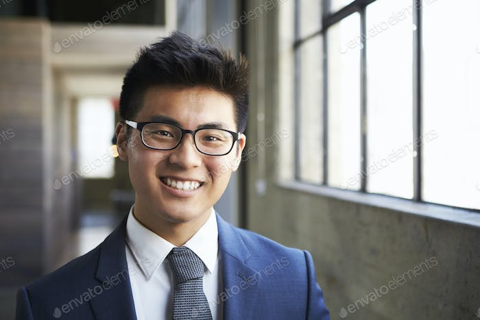 Young Asian businessman smiling to camera