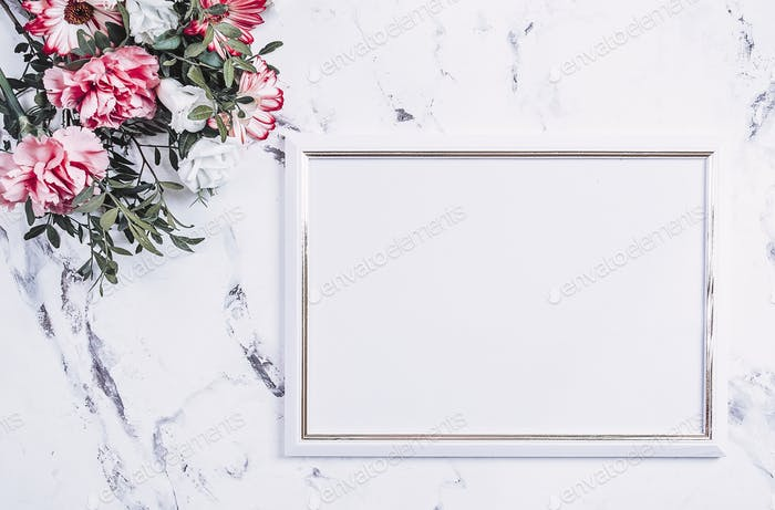 Blank frame and pink flowers over marble table