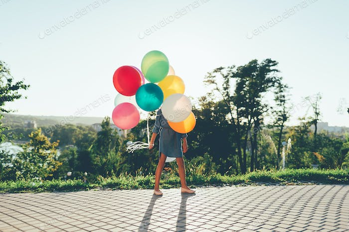 Girl holding colorful balloons in the city park, playing,