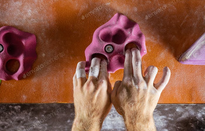 Closeup of rock climber's hands gripping handhold
