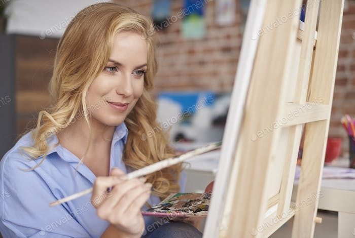 Woman painting in artists studio