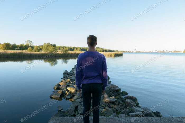 Rear view of young man looking towards the lake