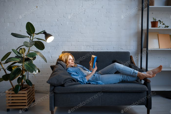 Young woman lying on cozy couch and reading a book