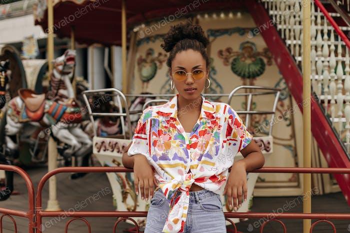 Junge attraktive dunkelhäutige brünette lockige Frau in Jeans, bunter Bluse und orangefarbener Sonnenbrille