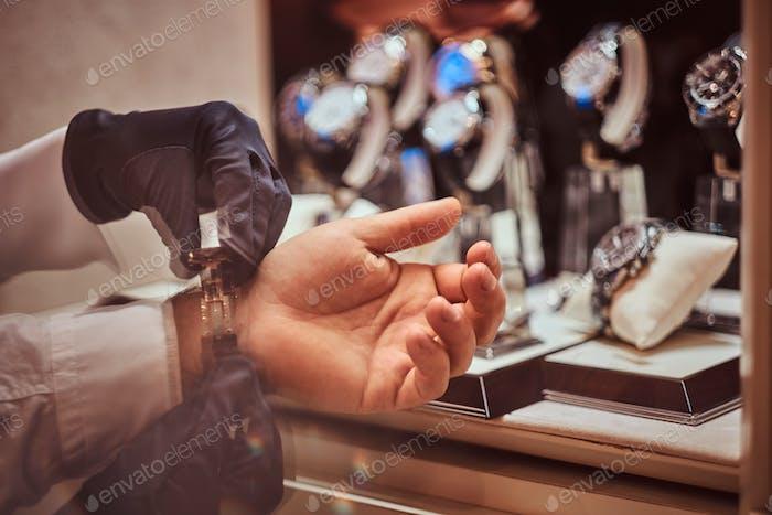 Nahaufnahme Hände. Assistant hilft dem Kunden, exklusive Herrenuhren anzuprobieren.
