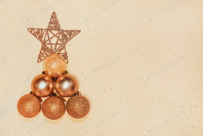 Christmas tree made of golden baubles and star on beige background