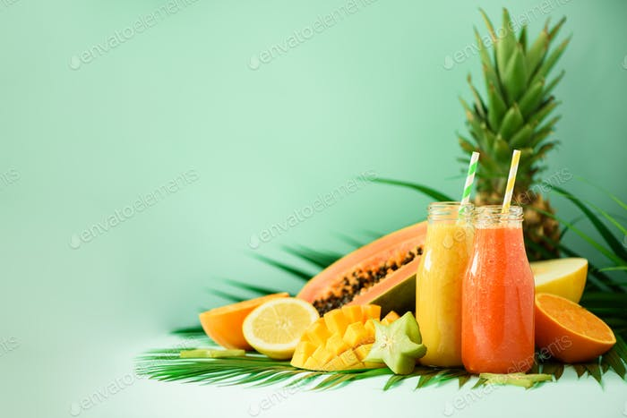 Juicy papaya and pineapple, mango, orange fruit smoothie in two jars on turquoise background. Detox