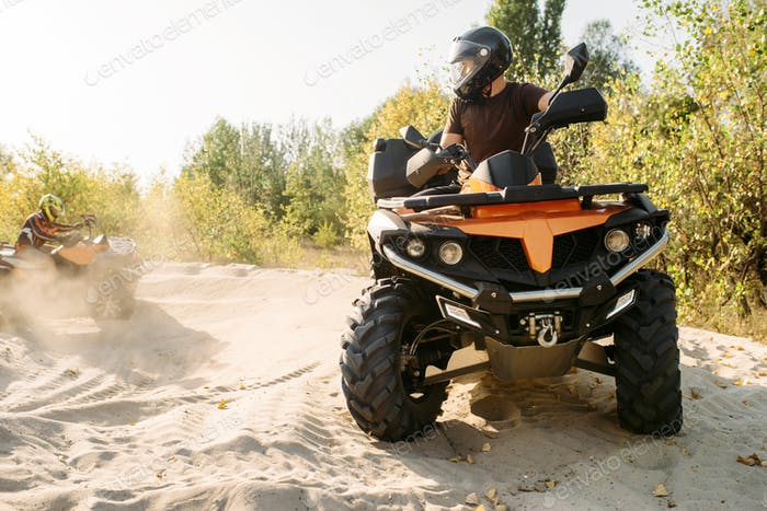 Two atv riders in helmets ride in a circle on sand