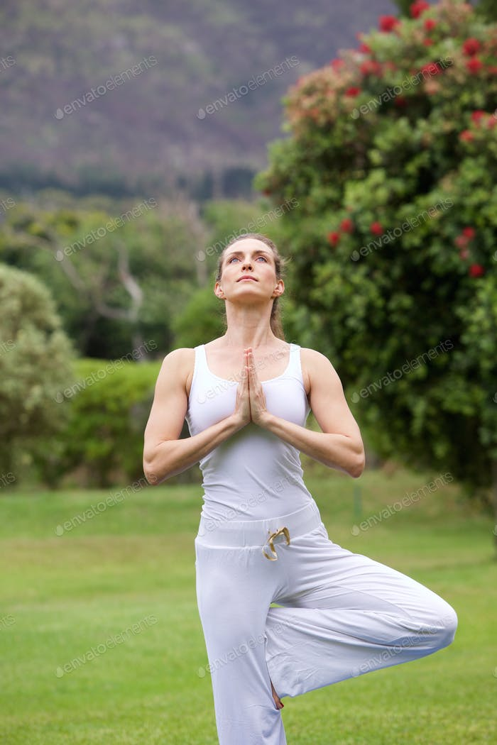 Yoga woman exercising outside in park