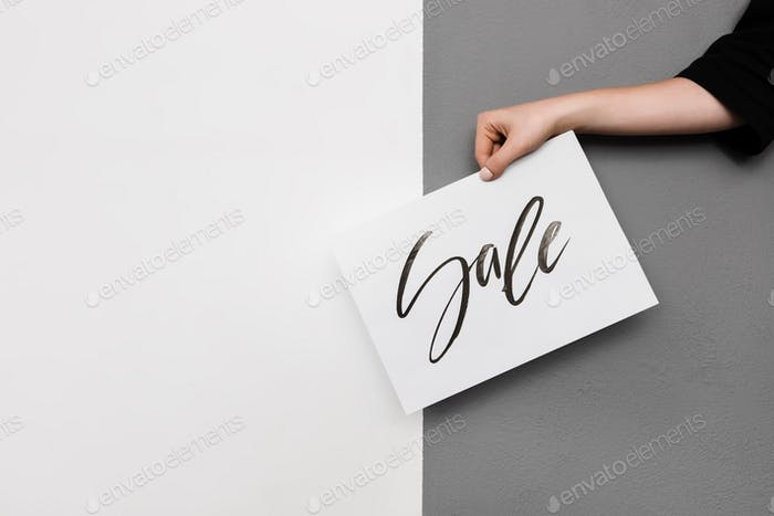 Close up photo of woman hand holding cool postcard on gray background