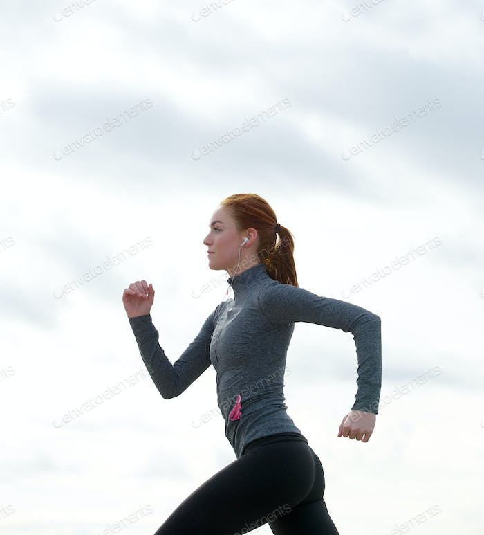 Healthy fit young woman running outdoors